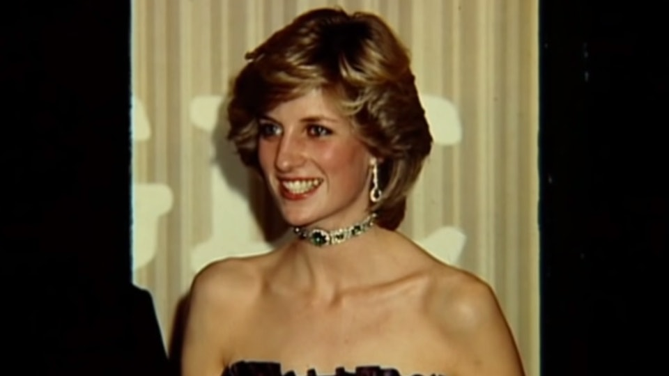 Princess Diana smiles in a black dress