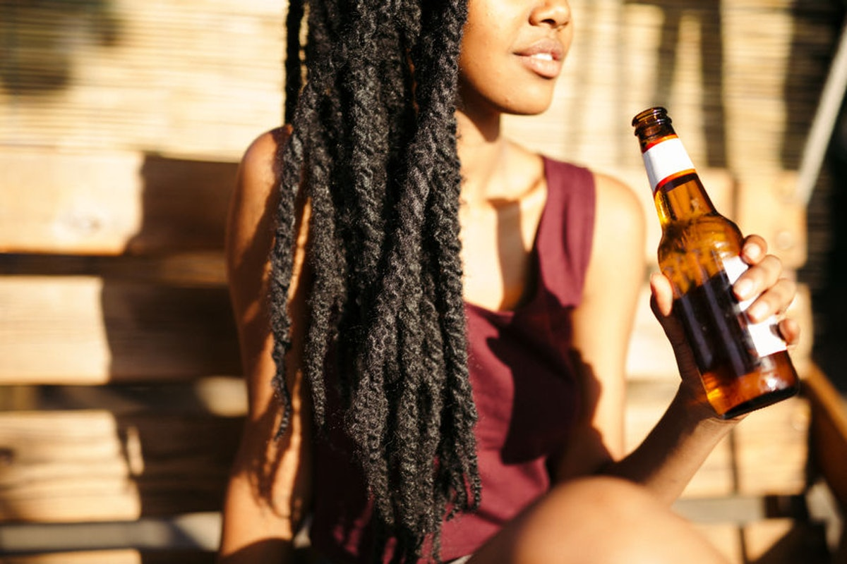 A woman is sitting in the sunshine with a bottle of beer in her hand.