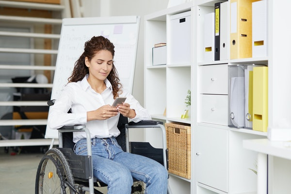 woman in wheelchair texting partner a check in text during the day