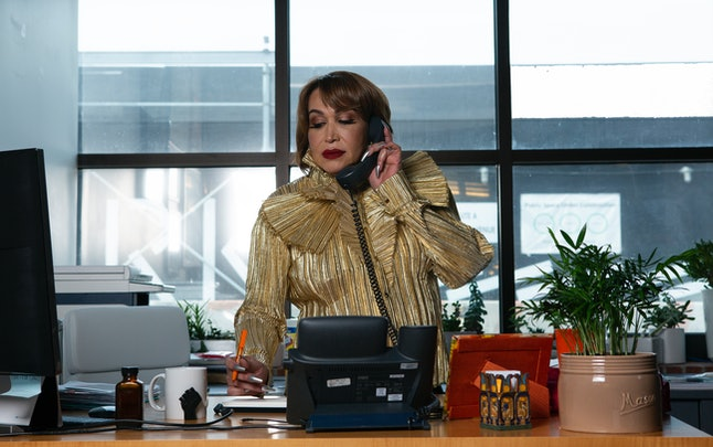 A trans woman executive takes notes while talking on her office phone, standing at her desk. Treating your colleagues like they're irreplaceable can go a long way toward maintaining a healthy work environment.
