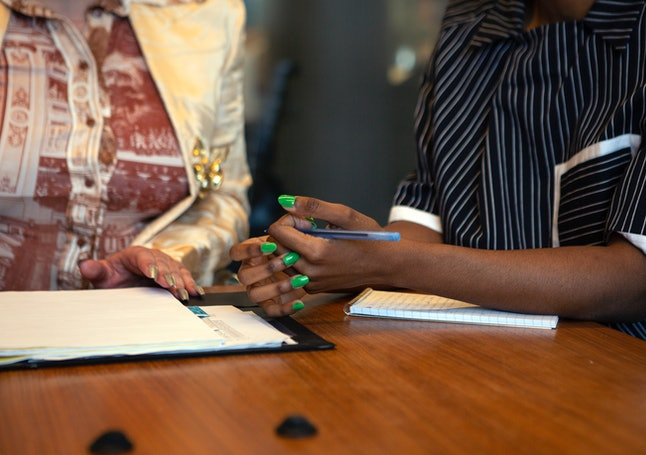 Two colleagues talk gently with their hands, holding pens and paper over their notebooks at work. Working together as a team can improve your work environment.