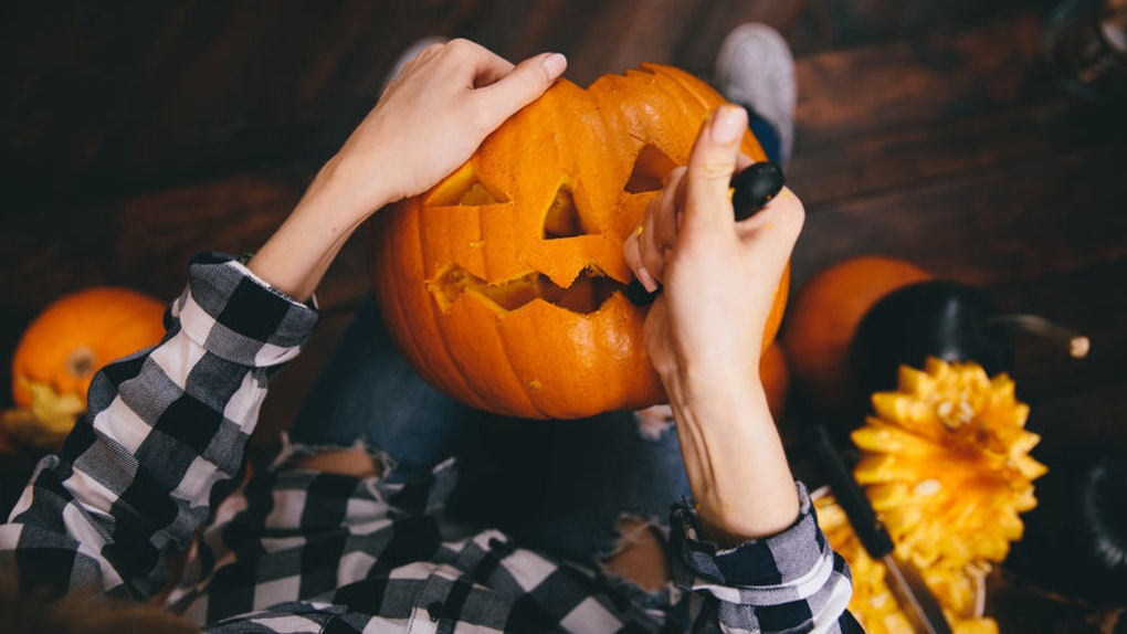 Woman wearing a flannel and carving a pumpkin makes for a great pose to pair with Instagram captions for pumpkin carving photos.