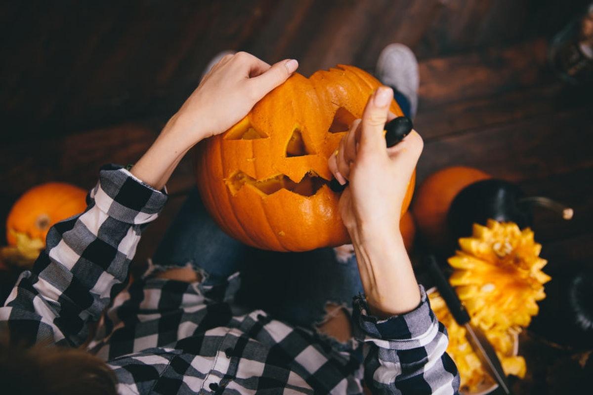 Woman wearing a flannel and carving a pumpkin makes for a great pose to pair with Instagram captions...