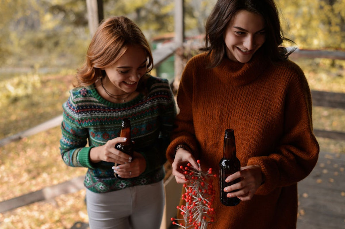 Two women are drinking beer and laughing on a fall day at a cabin.