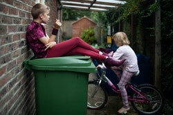 A transgender girl sits on a garbage bin in an alley with her sister on a bicycle.