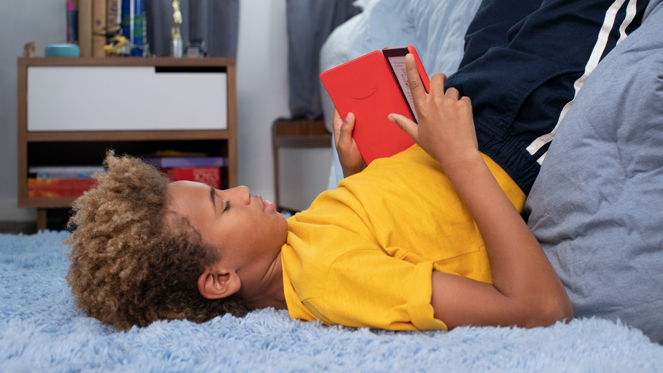 teen tween boy reading book in his room, amazon kindle kids