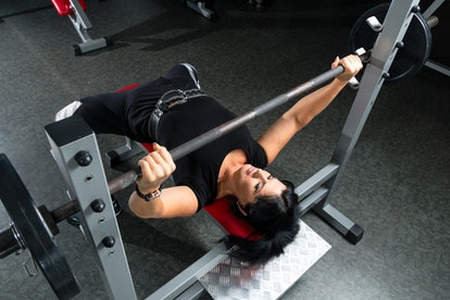 A person wearing a lifting belt prepares to unrack a heavy bench press. Working with a personal trainer is like hiring a client: interview your personal trainer like they're at a job interview to make sure they're a good fit for you.