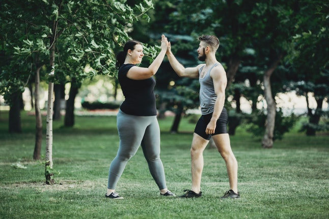 Two people high five each other after working out on a grassy field. Remember that only you can determine your goals, so be upfront with your personal trainer about what you want, not what you think they want to hear.