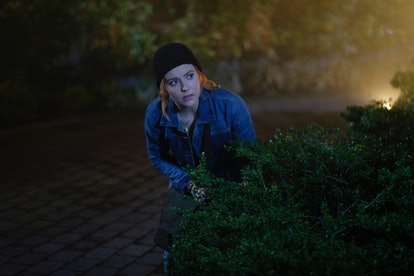Kennedy McMann as Nancy Drew lurks behind a bush about to break in a house in the CW's Nancy Drew