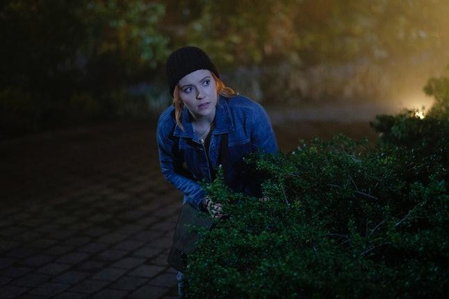 Kennedy McMann as Nancy Drew lurks behind a bush about to break in a house in the CW's Nancy Drew