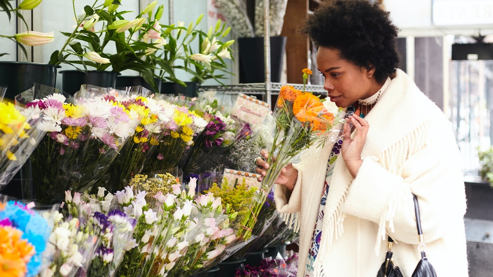 A woman sniffing flowers, enjoying being alone