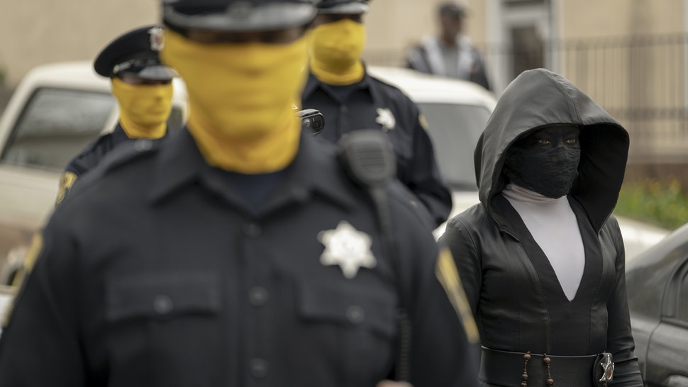Masked Tulsa police officers and Regina King as Angela Abar/Sister Night in HBO's Watchmen