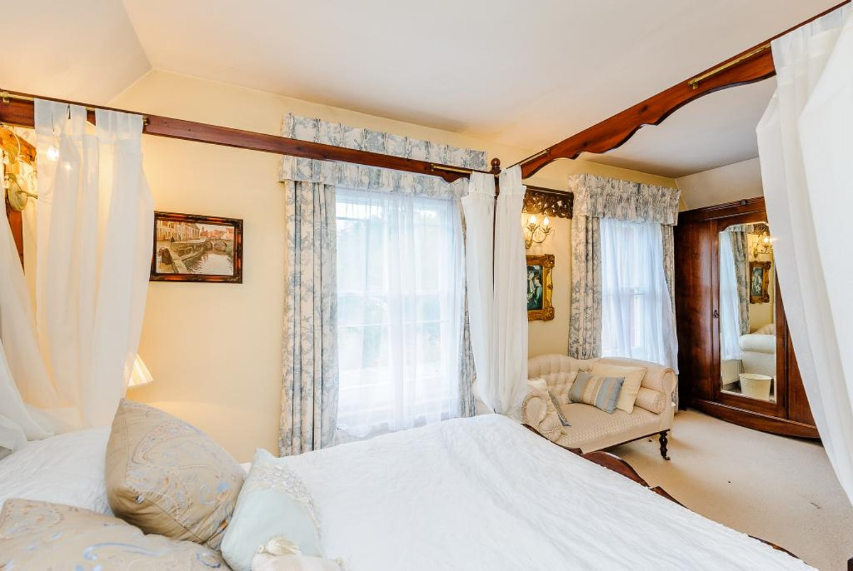 A beautiful vintage bed is next to a neutral-colored couch and window with light pouring through int...
