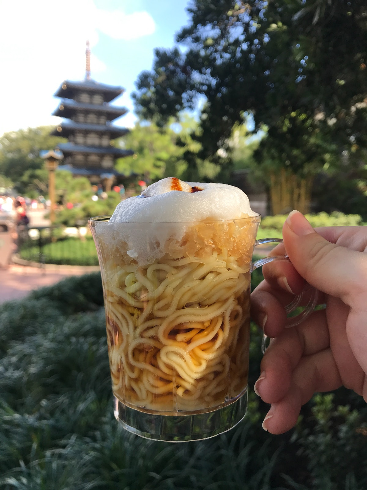 A woman's hand holds up a cup of chilled ramen with froth on top at Disney's Food & Wine Festival at Epcot.