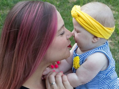 Mother with pink hair kisses baby