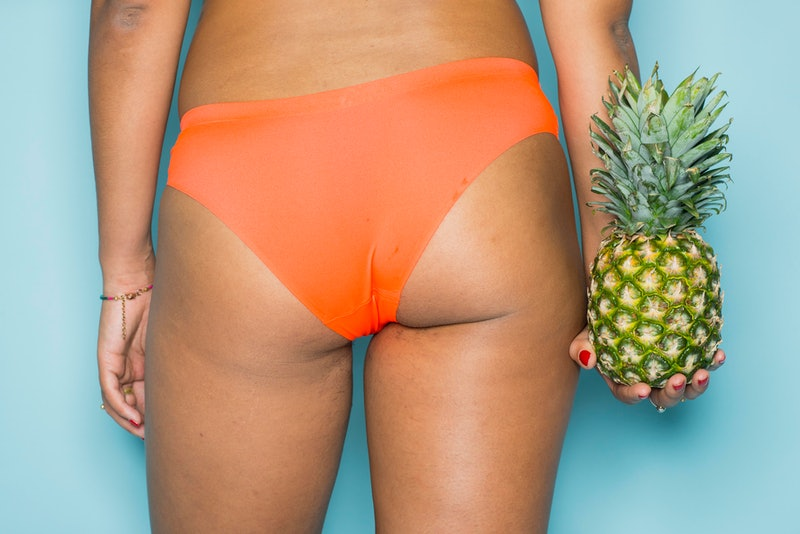 A woman stands with her back to us, holding a pineapple. Vagina smells vary from person to person, but shouldn't be too much of a cause for concern
