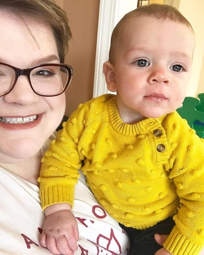 A mother holds up her toddler, who is wearing a bright yellow top.