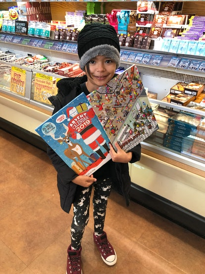 The author's daughter holds up two Trader Joe's advent calendars, including one for pets.