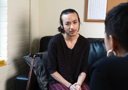 A genderqueer person sitting on a therapist's couch, listening. Gender-affirming medical care and socially transitioning can dramatically decrease high rates of trans depression and suicidality.