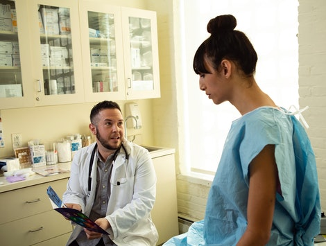 A transgender woman in a hospital gown speaking to her doctor, a transgender man, in an exam room. Gender-affirming surgery improves trans people's mental health, study says.