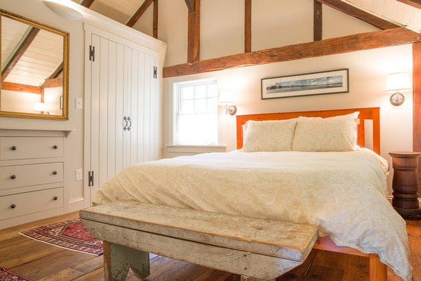 The bedroom of a loft carriage barn apartment in Kennebunkport, Maine has wood details and warm lighting.