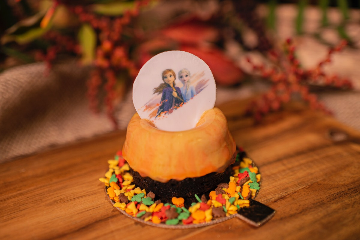 The Fall Into Winter Dessert cake — which is orange and has leaf-shaped sprinkles on the bottom — is...