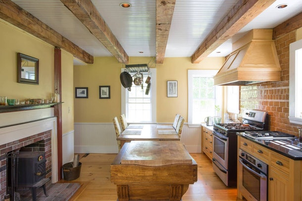 The kitchen of a 1780 farm house in Kennebunkport, Maine has a wooden table and indoor fireplace.