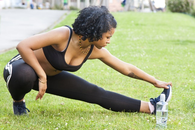 A person stretches her leg on a grassy field with her water bottle nearby. Experimenting with some sprints can help keep your treadmill workout feeling both enjoyable and challenging.