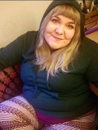 A woman in a hoody sits on a couch