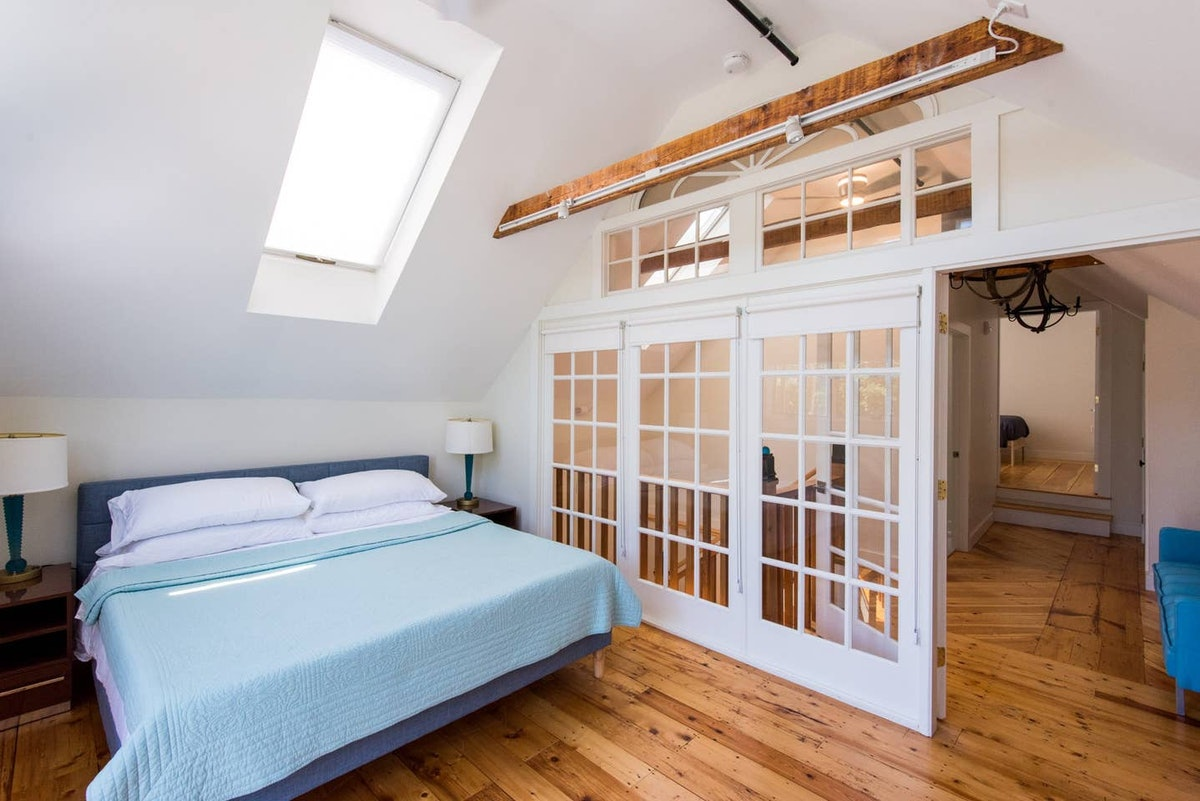 The bedroom of a pet-friendly loft apartment in Kennebunk, Maine has a skylight and comfortable bed.