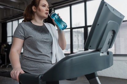 A person cools down from a treadmill workout with a blue water bottle. Make sure you're warmed up before you hop on the treadmill, and then playing some fun mental games with yourself might help you enjoy your workout.