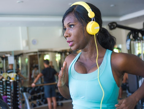 A person with yellow headphones and a blue tank top sweats as she runs on a treadmill. If you're bored with your treadmill workouts, there are ways to make your session much more fun.