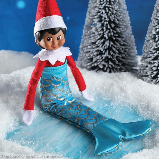 A picture of an elf with red eyes and brown hair wearing a mermaid's tail, probably about to swim away from Christmas.