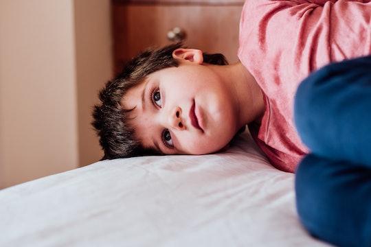 Boy lies in bed pretending to be sick