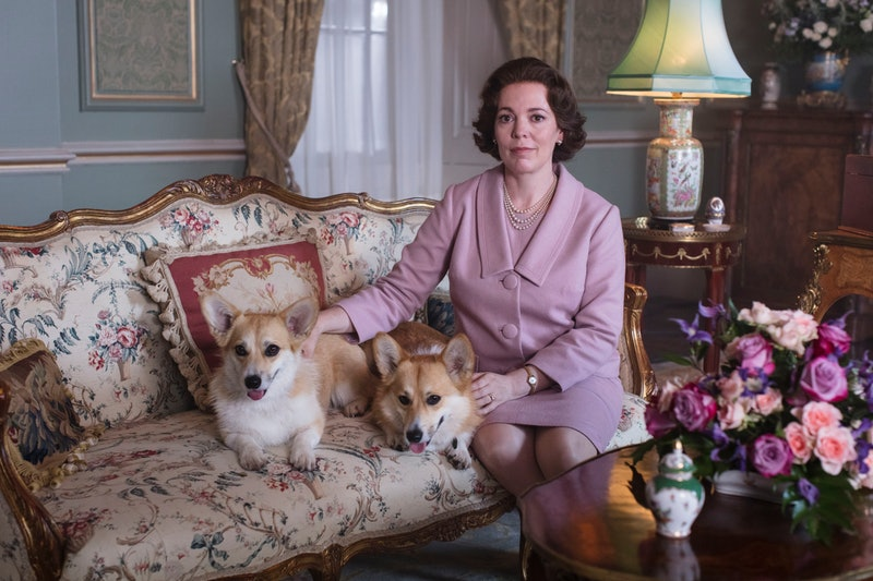 The Queen and her corgis sitting on a couch on The Crown