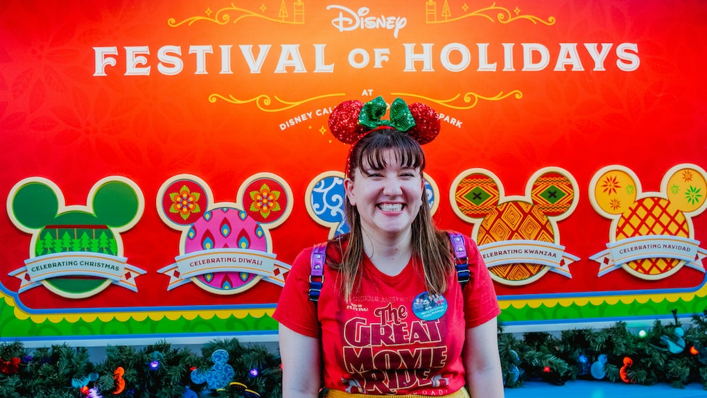 Woman wearing Minnie Ears standing in front of the Festival of Holidays sign at Disney's California Adventure.