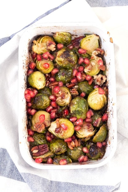 A white dish with roasted brussel sprouts sprinkled with pomegranate seeds and pecans. Veggies can m...