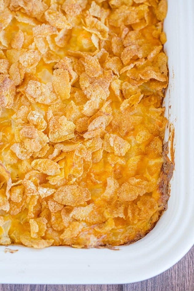 Easy Thanksgiving dishes; baking dish full of cheesy potato casserole with corn flake topping