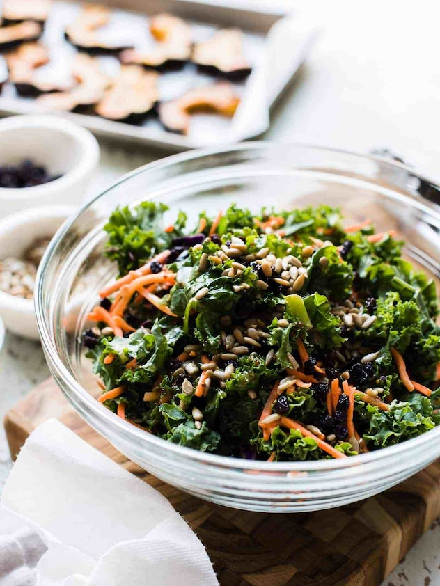 Easy Thanksgiving dishes; bowl of roasted acorn squash and kale salad on a cutting board