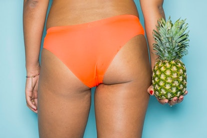 A woman in orange underwear holding a pineapple. Bidets may have health benefits for cleaning your anus.
