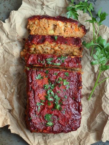 A glazed vegan meatloaf, partially sliced. Chickpea vegan meatloaf is a great option for a vegan Tha...