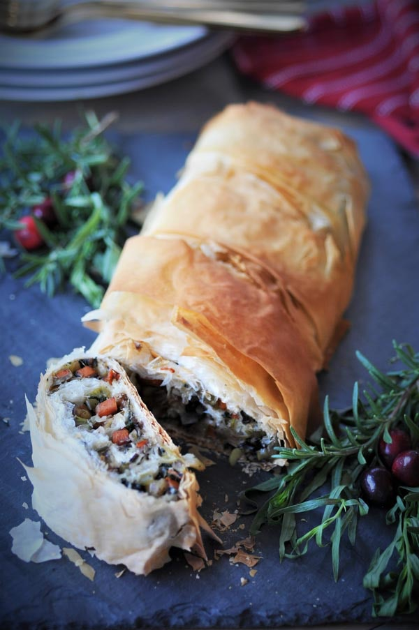 A few sliced pieces of vegan wellington laying next to the rest of the loaf. A great combination of pie and veggies makes a great vegan Thanksgiving entree.
