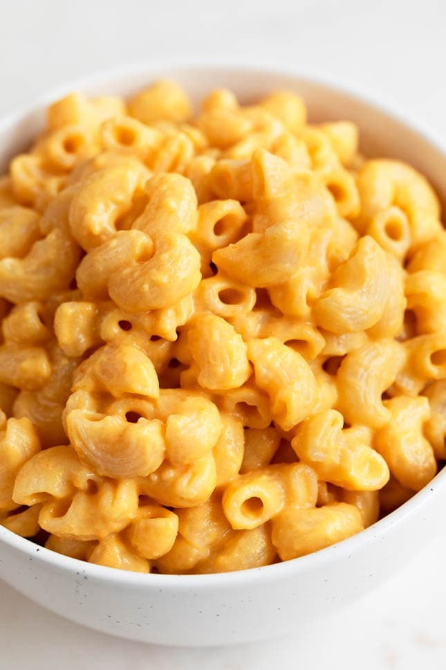 A close-up image of a white bowl full of vegan mac and cheese. You don't need cheese to make an excellent vegan mac and cheese for Thanksgiving.