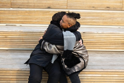 Two transmasculine friends embracing while sitting down. Practicing self-love and supporting each other during Trans Awareness Week is important for trans and non-binary people.