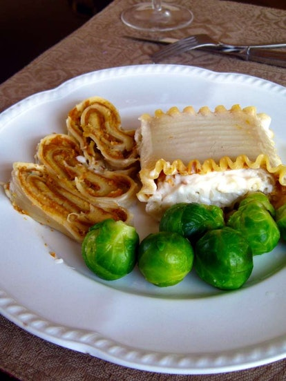 A white plate with a few slices of vegan pumpkin lasagna and brussel sprouts. Vegan main dishes don'...