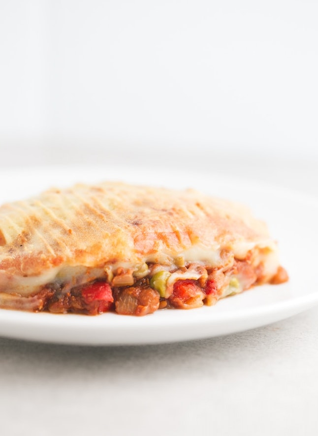 A veggie-filled vegan shepherd's pie sits on a white plate with a white background. You don't need meat to make this meat-less, dairy-free shepherd's pie for Thanksgiving.