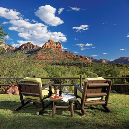 Two wooden lawn chairs and a matching table are on a lawn overlooking red rock mountains in the dist...