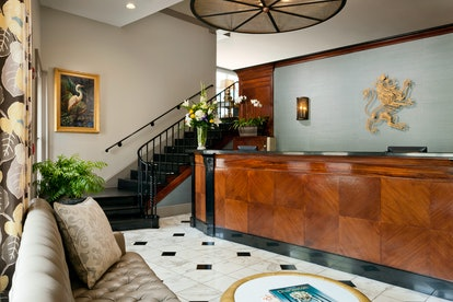 A luxe hotel lobby with a glossy wooden reception desk, marble floors, and a black staircase leading...