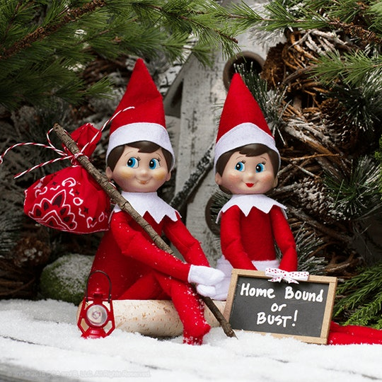 """When Does Elf on the Shelf Start; two elves sitting by a Christmas tree in the snow with a sign reading """"Home Bound or Bust!"""""""