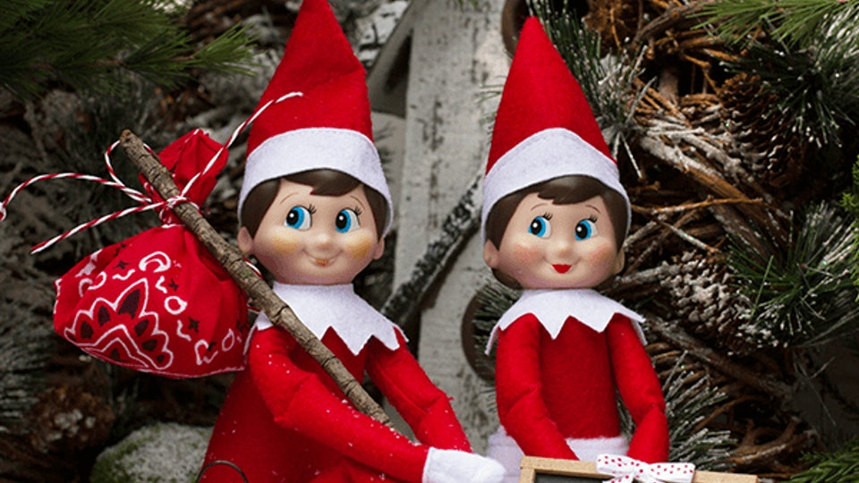 "When Does Elf on the Shelf Start; two elves sitting by a Christmas tree in the snow with a sign reading ""Home Bound or Bust!"""